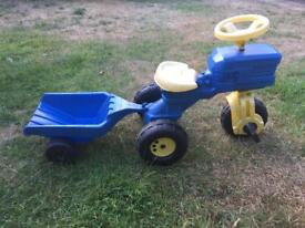 Blue ride on tractor with trailer.