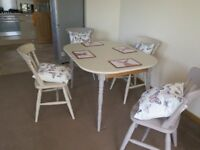 Two tone dining table and four chairs. Extendable and comes with new cushions and placemats
