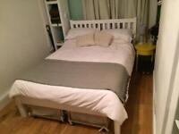 White wooden double bed with mattress