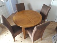 Rustic solid oak circular extendable dining table in immaculate condition, with 4 faux suede chairs