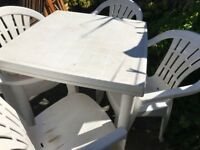 White plastic garden table and four chairs.