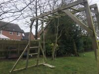 Wooden monkey bars includes swing and rope attachment.