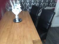 Lovely solid table with 6 black leather chairs