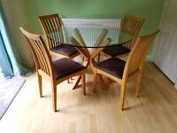Solid oak and glass dining table and four chairs