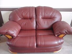 Leather two seater settee in chestnut brown with wood trim in good condition.