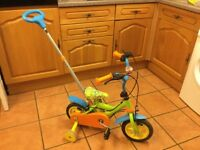 A toddlers bike with an adult handle
