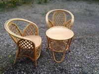 Cane round table and two cane chairs