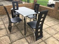 smoked glass table and four high back chairs,