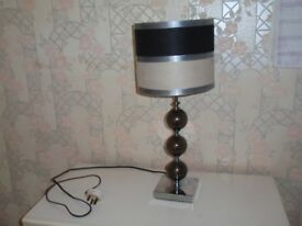 Lamp with stripey shade and ball design stand