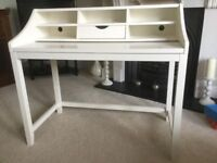 White desk with pull out central drawer and extending desk top. 5 spaces for papers, pens etc