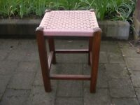 A wood framed foot stool with woven cord seat.