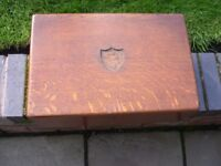An oak storage box with metal recessed side handles.