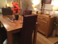 Solid oak dining room table with extension leaf, 8 chairs and solid oak side board for sale.
