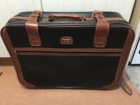 Large leather effect vintage suitcase on wheels with buckles
