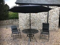 Circular glass topped garden table, with parasol and 4 chairs
