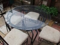 metal table and 4 chairs in good condtion seat could do with covering or new cloth on them