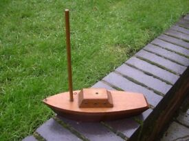 A small solidly built model wooden boat with sail mast.