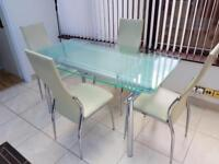 GLASS EXTENDING DINING TABLE AND 4 FAUX LEATHER CHAIRS