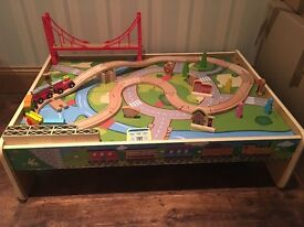 Wooden train table with track and accessories.