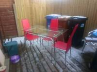 Glass dining table and 4 red chairs