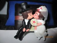 Wedding cake topper, bride & groom on a bench