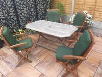 Garden table 4 folding chairs and cushions the table is wooden folds up the chairs also fold up