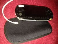 Black PSP, unboxed, with charging adapter