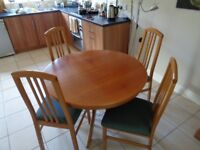 Extending round dining table and four chairs