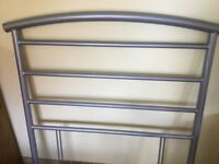 A silver, metal headboard for a single bed.
