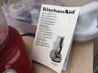 A Kitchenaid food processor with unused accessories and book