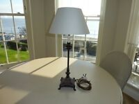 Soliid brass candlestick-type table lamp with pale grey card shade.