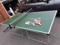 Table tennis table with paddles, balls and net