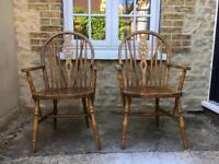 Pair of solid wood wheelback carver chairs with armrests