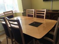 Wooden extending dining table with six upholstered chairs.