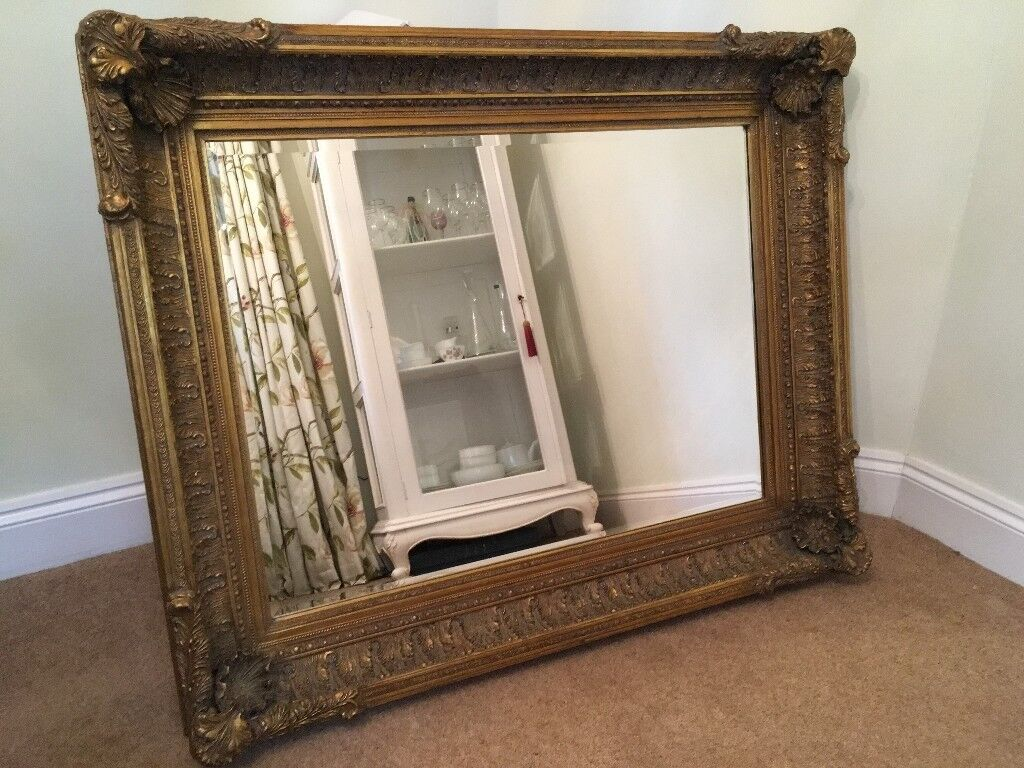 A large mirror encased in a beautiful, ornate heavy wooden frame ...