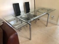 Glass dining table with 4 black chairs