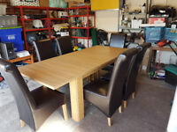 Extending oak dining table with 8 Faux leather chairs
