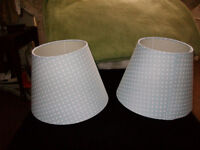 A pair of pale blue lampshade with white spots