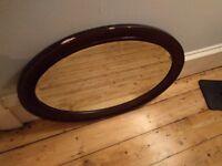 Oval mirror with dark wood effect fibreglass frame