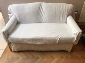 Two seater sofa bed with throw