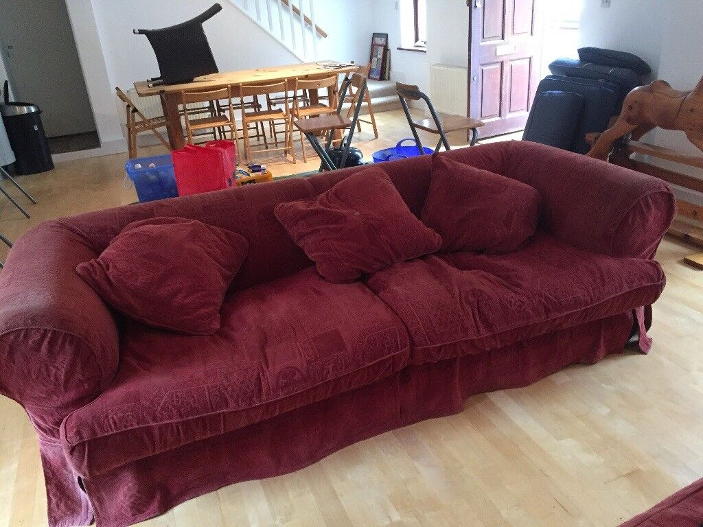 3 large burgundy sofas with a foot stool