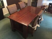 Beautiful solid wood dining table and six high back rattan/weave chairs.