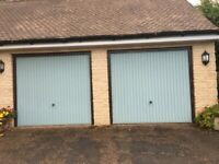 A pair of electric up/over garage doors.