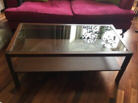 Dark wood coffee table with glass top and lower shelf.