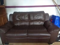 Two chocolate brown faux-leather sofas