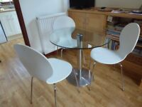 Glass and chrome table, suitable for a small area in a kitchen. 80 cms diameter.