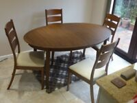 Solid wood extendable dining table with 4 upholstered high-back chairs.