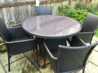 Brown rattan glass topped table and four chairs.