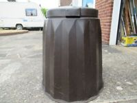 Brown , plastic compost bin with lid .
