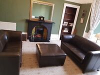 Formal leather sofas and pouffe.